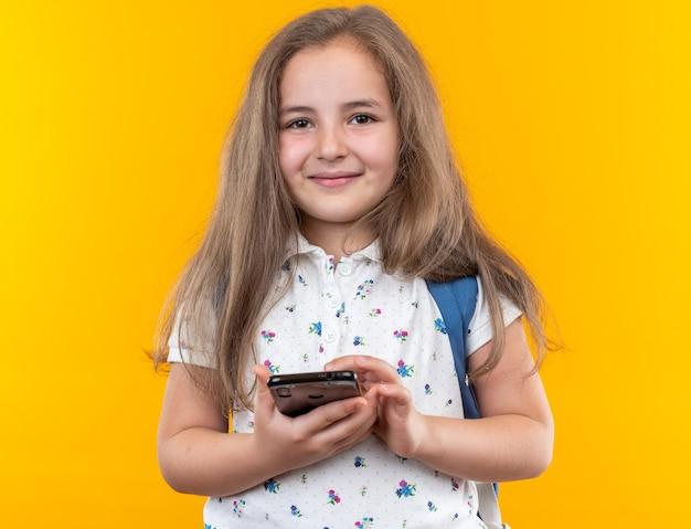 Een klein mooi meisje met lang haar met een rugzak die een smartphone vasthoudt, blij en vrolijk lachend op oranje
