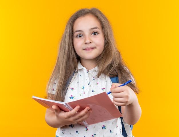 Een klein mooi meisje met lang haar met een rugzak met een notitieboekje en een pen, blij en positief glimlachend staande op oranje