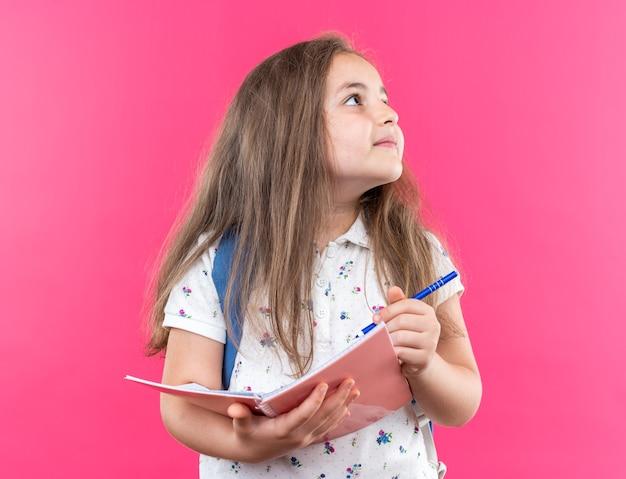 Een klein mooi meisje met lang haar met een rugzak met een notitieboekje en een pen die omhoog lacht en vrolijk op roze staat