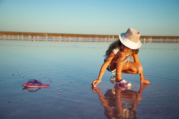 Een klein mooi meisje met prachtig golvend haar kijkt naar iets in een transparante waterige glazuur op een transparant oppervlak