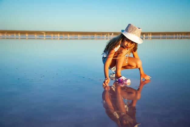 Een klein mooi meisje met prachtig golvend haar kijkt naar iets in een transparante waterige glazuur op een transparante achtergrond
