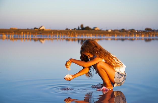 Een klein mooi meisje met prachtig golvend haar kijkt naar zout in een transparante waterige glazuur op een transparant oppervlak