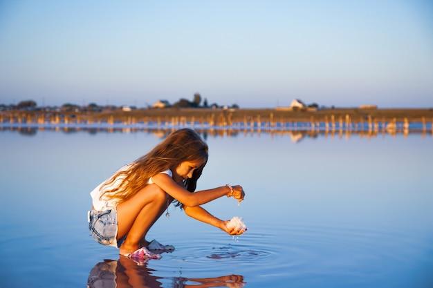 Een klein mooi meisje met prachtig golvend haar kijkt naar zout in een transparante waterige glazuur op een transparante achtergrond