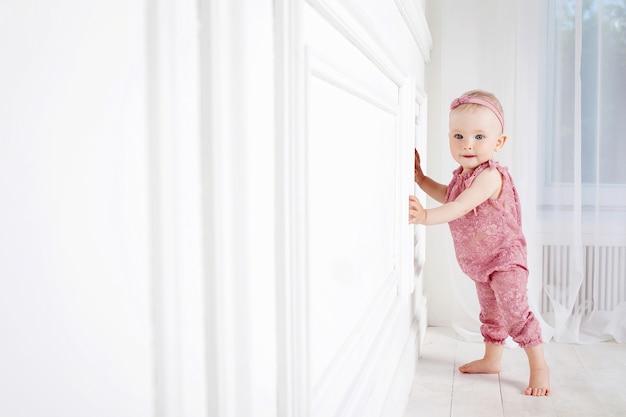 Een klein mooi meisje van 1 jaar zet de eerste stappen.