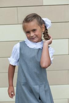 Een klein mooi schoolmeisjesmeisje past haar haar aan. kapsel met een vlecht en strikken. een eersteklasser. kennis dag. terug naar school