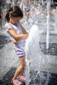Een klein nat meisje koelt af in een fontein op een hete zomerdag.