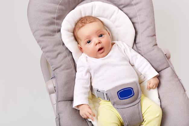 Een klein pasgeboren meisje ligt in een babyschommelstoel