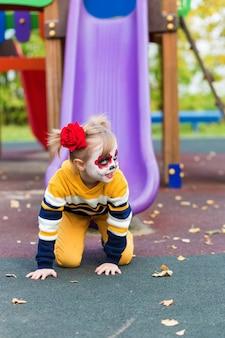 Een klein peutermeisje met geverfd gezicht, rijdt op een glijbaan op de speelplaats, viert halloween of mexicaanse dag van de doden.