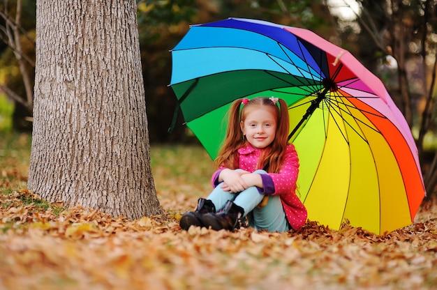 Een klein roodharig meisje in een roze jasje zit op gele bladeren met een grote paraplu van regenboogkleur.