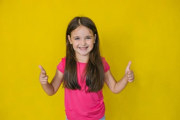 Een klein schattig blij meisje, kijkend naar de camera en met een teken van goedkeuring,