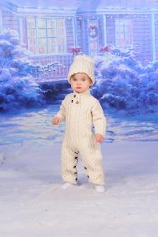 Een klein schattig kind staat in de sneeuw in een gebreid pak.