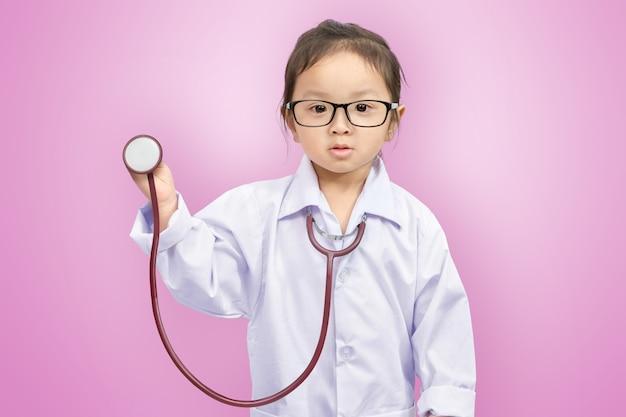 Een klein schattig lachend meisje in eenvormige arts met een stethoscoop