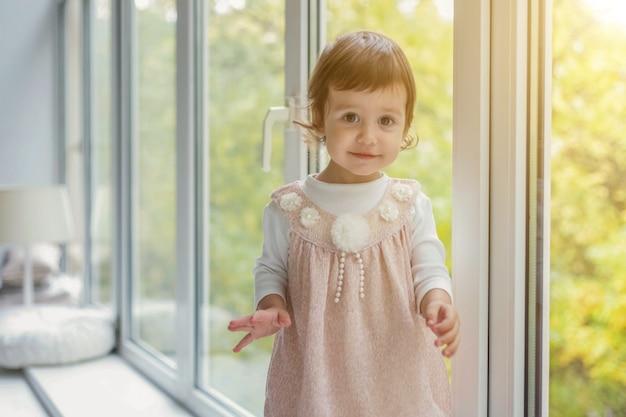 Een klein schattig lief lachend meisje in een pastelroze jurk die op de vensterbank staat in een fel lichte woonkamer thuis en glimlacht. jeugd, kleuterschool, jeugd, ontspannen concept