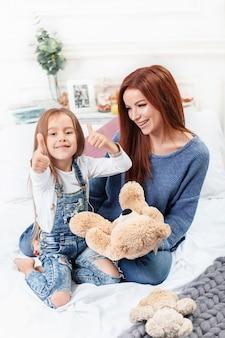 Een klein schattig meisje dat geniet, speelt en creëert met speelgoed met moeder