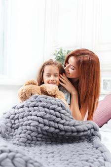 Een klein schattig meisje genieten, spelen en creëren met speelgoed met moeder