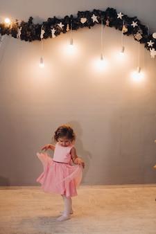 Een klein schattig meisje in een jurk met krullend haar kijkt naar haar jurk bij de slinger