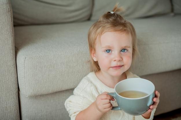 Een klein schattig meisje in een oranje trui drinkt thee. gezellig portret van een girlsitting thuis. vallen.