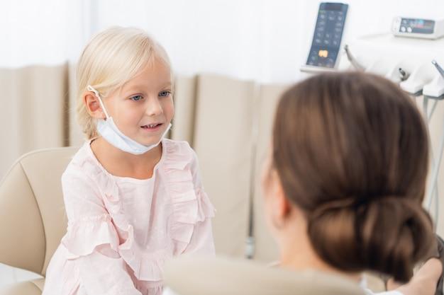 Een klein schattig meisje luistert naar de aanbevelingen van haar arts na een controle