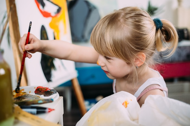 Een klein schattig meisje schildert thuis een grote foto met acryl op een ezel