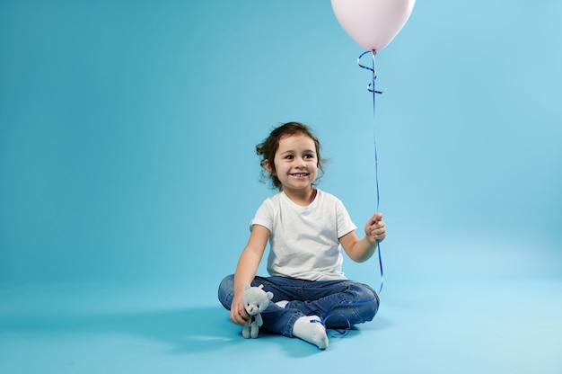 Een klein schattig meisje zit op een blauw oppervlak en houdt een roze ballon in de ene hand en een knuffelbeer knuffel in de andere hand