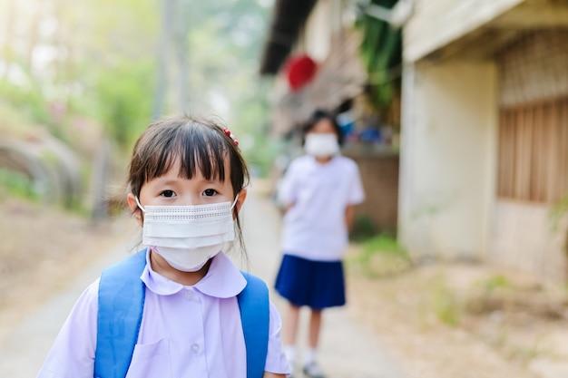 Een klein schoolmeisje heeft een masker dat zichzelf beschermt tegen het corona-virus covid-19 wanneer het kind naar school gaat