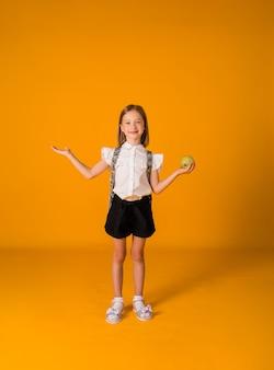 Een klein schoolmeisje in een uniform en met een rugzak staat en houdt een appel vast op een gele achtergrond met een kopie van de ruimte