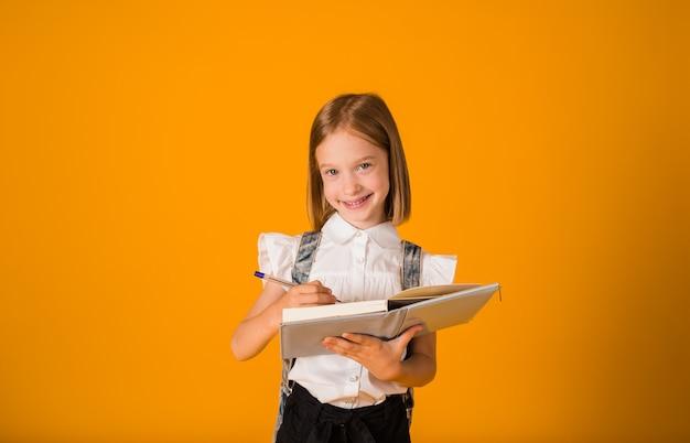 Een klein schoolmeisje in een uniform heeft een blauw notitieboekje op een gele achtergrond met een plek voor tekst