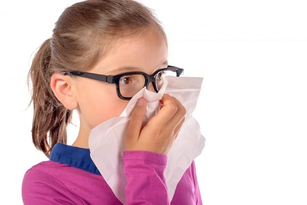 Een klein schoolmeisje is verkouden