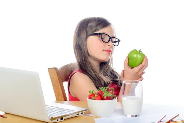 Een klein schoolmeisje kijkt appel
