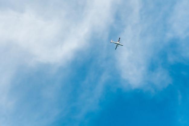 Een klein silhouet van een vliegtuig in een blauwe lucht met witte wolken