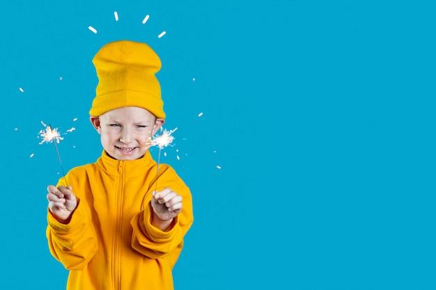 Een klein vrolijk kind in een gele hoed en jas houdt brandende sterretjes in zijn handen op blauwe achtergrond