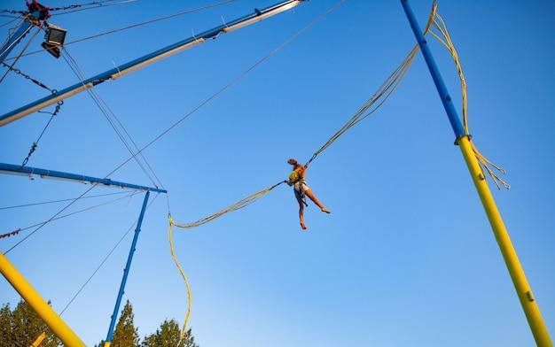 Een klein vrolijk meisje vliegt op verende, heldere elastische banden en springt op een trampoline, genietend van de langverwachte vakantie in de warme zon