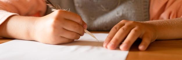 Een klein zevenjarig meisje tekent een verdwijnende tekening op papier met een echte geslepen eendenpen met melk in plaats van inkt. banier