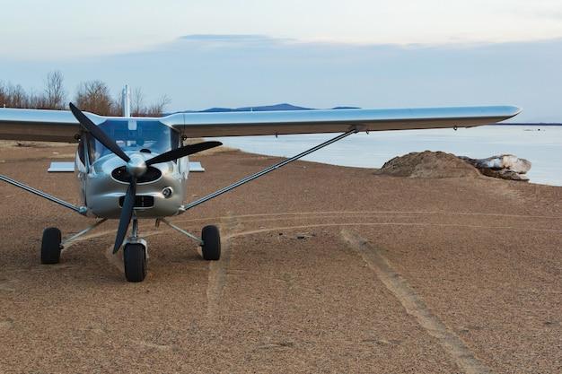 Een klein zilveren vliegtuigje landde op de zanderige kust van een riviereiland