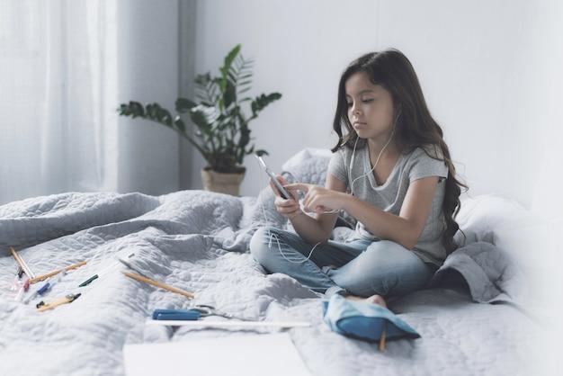 Een klein zwartharig meisje zit op een bed in het wit