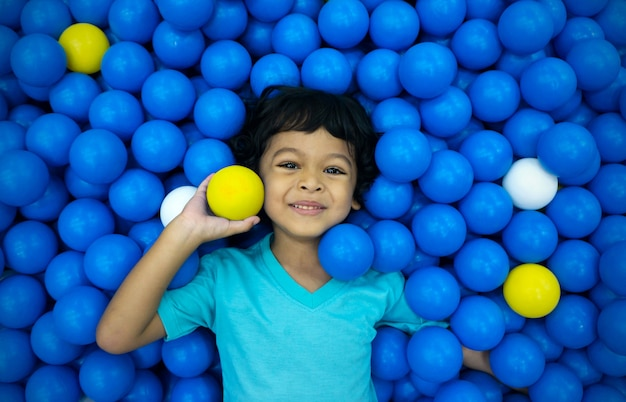 Een kleine aziatische jongen speelt met veel blauwe en gele ballen