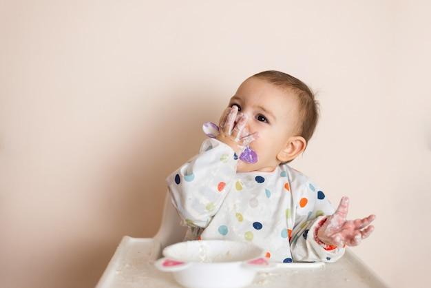 Een kleine baby die haar eten eet en een zooitje maakt met yoghurt en ontbijtgranen