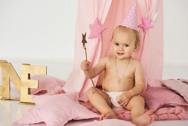 Een kleine baby in een roze tent met een toverstaf in de buurt van een grote taart.