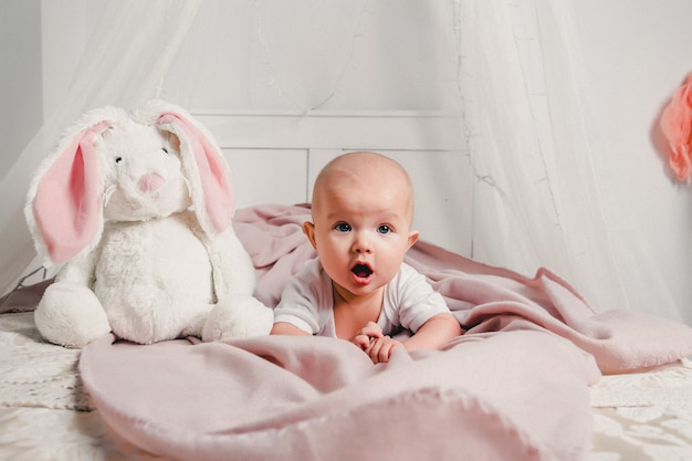 Een kleine baby legt op een bed met een speelgoedkonijn en glimlacht