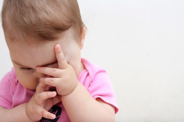 Een kleine baby wrijft in zijn ogen. moe baby wil slapen. baby dag modus concept