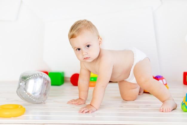 Een kleine babyjongen van zes maanden oud kruipt door in een lichtwitte kinderkamer in luiers tussen speelgoed