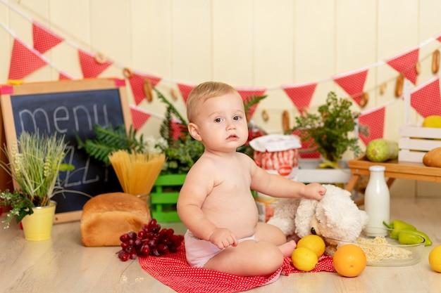 Een kleine babyjongen van zes maanden oud zit op de grond tussen keukengerei en eten en voert een stuk speelgoed spaghetti