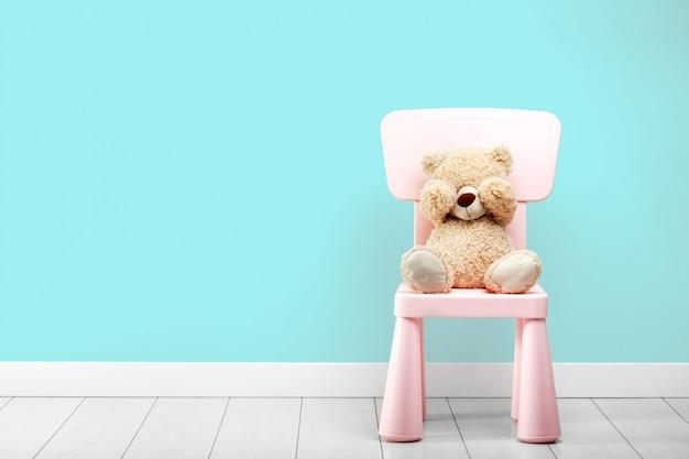 Een kleine beer zit in een turquoise kamer op een stoel met zijn ogen gesloten handen