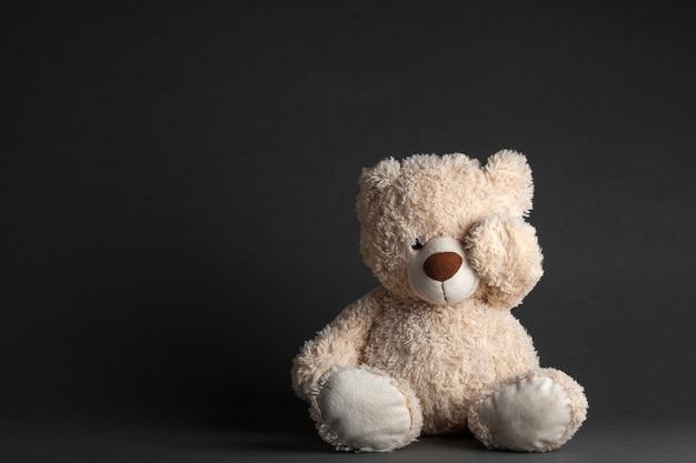 Een kleine beer zit in een zwarte kamer op een stoel met zijn ogen gesloten handen