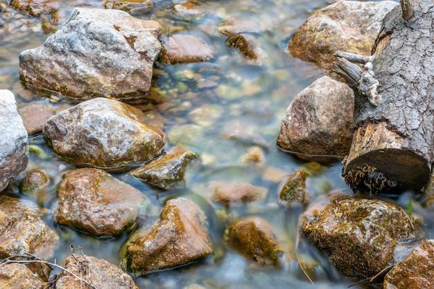 Een kleine bergbeek stroomt in het bos tussen de stenen