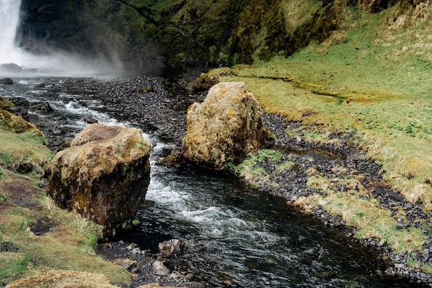 Een kleine bergrivier stroomt tussen twee rotsblokken