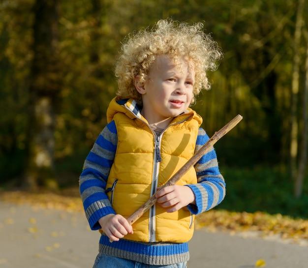 Een kleine blonde jongen die met een stok speelt