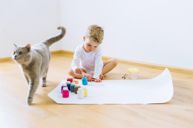 Een kleine blonde jongen schildert een papier met een kat