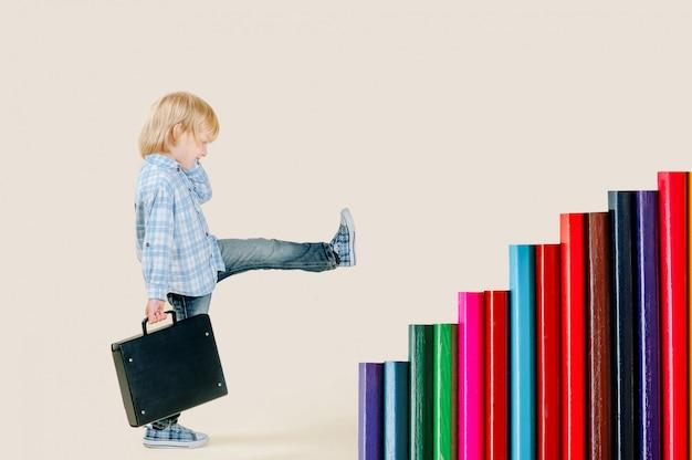 Een kleine blonde jongen van vijf jaar met een rugzak stapt de trap op uit potloden. surrealisme, het bereiken van doelen