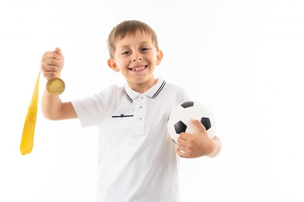 Een kleine blonde jongen wint en houdt voetbal en een gouden medaille, geïsoleerd beeld
